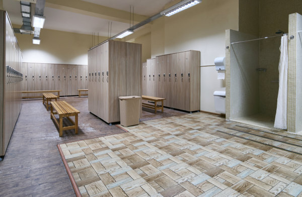 Public shower interior with everal showers, toilet sink and lockers in locker room.