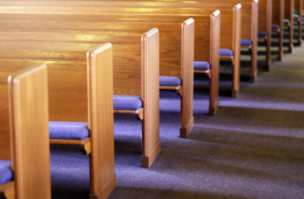 Window light is shing on rows of empty church pews in a Church