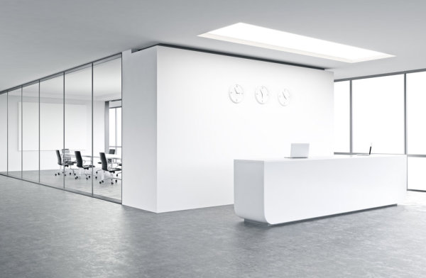 Empty office, white reception at white wall, three clocks on it.
