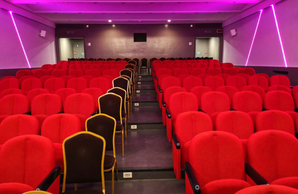 empty auditorium hall with red chairs