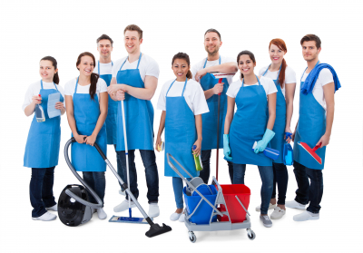 Large diverse group of janitors wearing blue aprons standing grouped together with their equipment smiling at the camera isolated on white