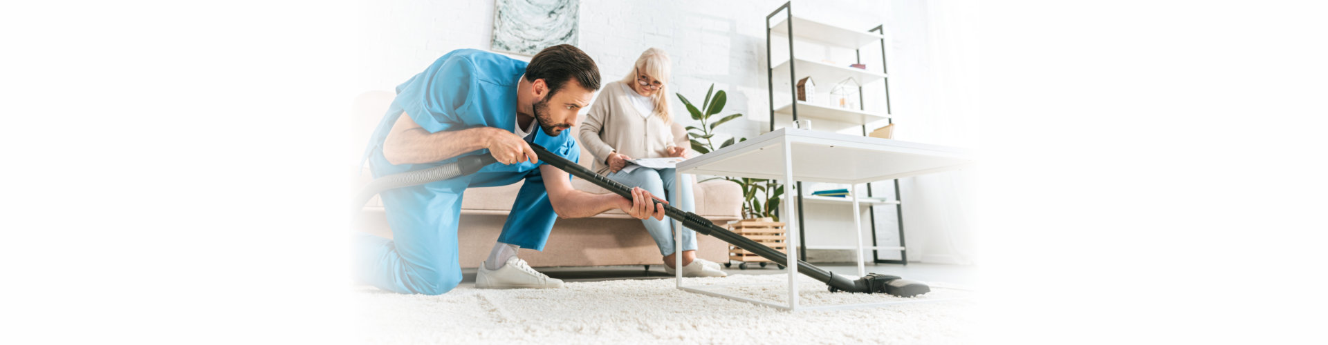 young man using vacuum cleaner while senior woman sitting on sofa